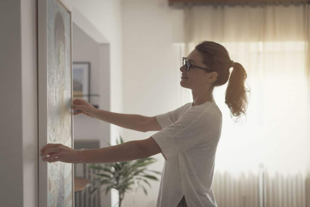 Woman hanging a painting at home